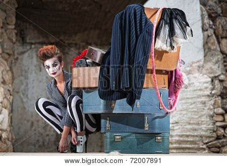 Grinning Clown Near Suitcases