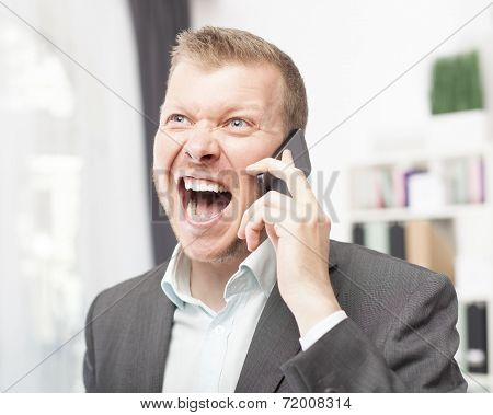 Exuberant Young Man Shouting In Reaction To A Call