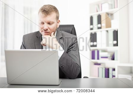 Man Looking At His Laptop With A Wry Expression