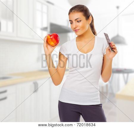 Young girl with apple and chocolate at light kitchen