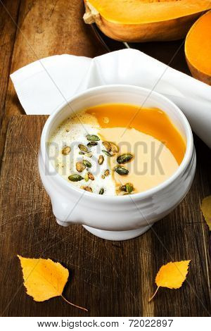 Pumpkin Soup In White Plate On Wooden Table With Pumpkin Seeds.