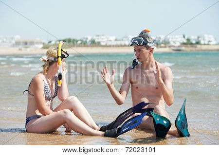 Young couple with snorkel gear sharing impressions on red sea beach at vacations
