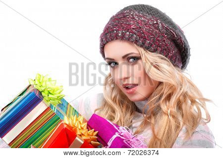 A photo of beautiful girl is in winter clothes with varicoloured gift boxes, isolated