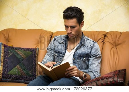 Handsome young man reading book at home, sitting on couch