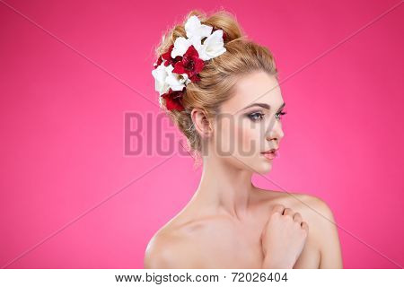 Beautiful girl, isolated on a pink background with varicoloured flowers in hairs, emotions, cosmetics