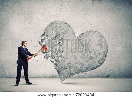 Young determined businessman crashing stone heart with axe