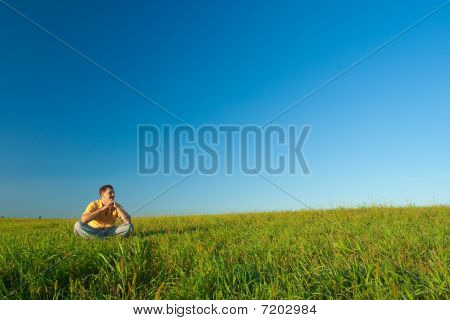 Young Man Sitting On Green Field