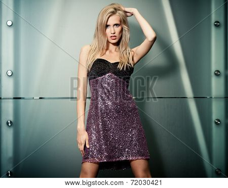 Beautiful lady in short dress posing in the night city