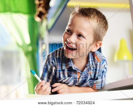 cute little boy in room studying and laughing