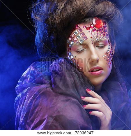Beautiful woman with bright creative make up in blue smoke