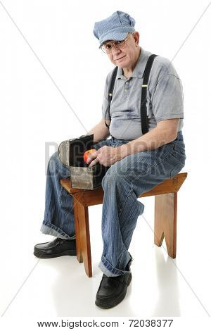 A senior train engineer smiling at the viewer as he removes an apple from his lunch pail.  On a white background.