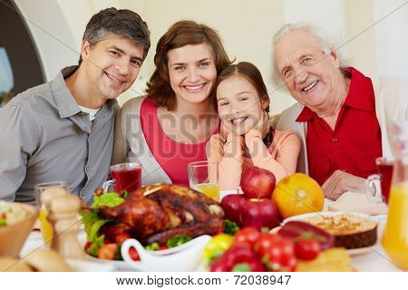 Happy family of four sitting at festive table on Thanksgiving day
