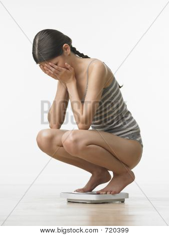 Woman Hiding Eyes On Scale