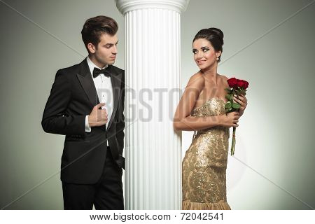 young elegant couple looking at each other near column, studio picture