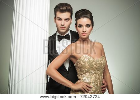 fashion elegant couple man in tuxedo and woman in evening gown standing embraced near column in studio