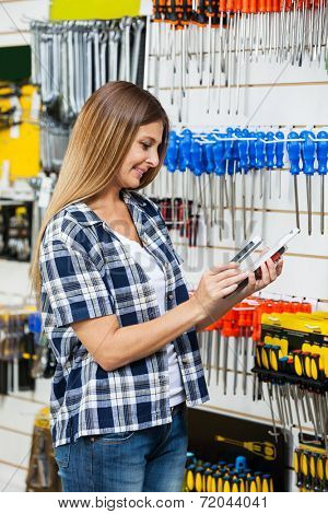 Female customer scanning product's barcode through mobilephone in hardware store