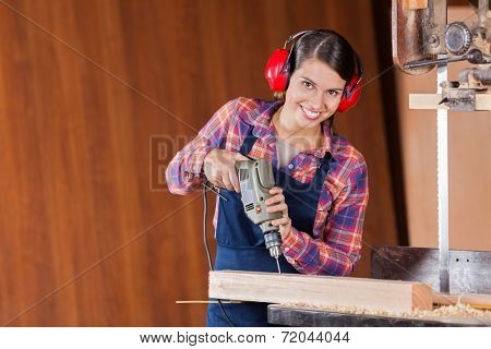 Portrait of confident female carpenter using drill machine on wood in workshop