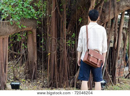 Back Of Fashionable Young Man With Leather Bag