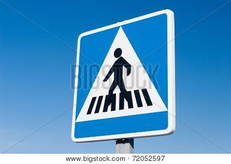 Pedestrian road sign against blue sky