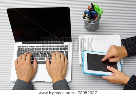 Top View Of Businesswoman And Businessman On Meeting Working With Tablet Computer And Typing On Lapt