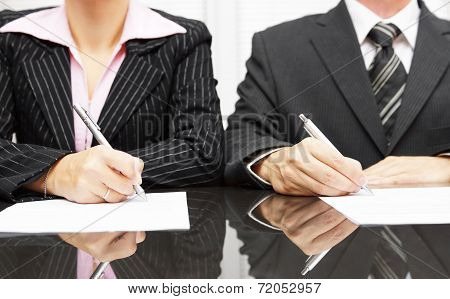 Businesswoman And Businessman Signing Contract After Negotiations
