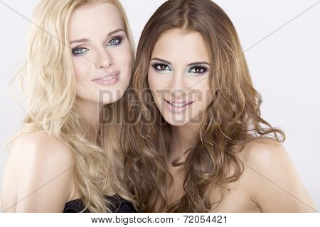 Cosmetics portrait of two smiling young adult attractive and sensuality girl friends - blonde and brunette on white background