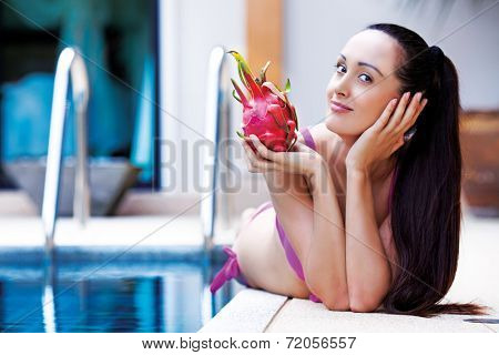 beautiful slim young  woman by the swimming pool with a dragon fruit