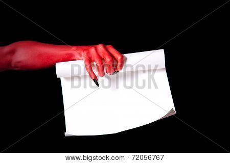 Red devil hand holding paper scroll, Halloween deal with devil concept