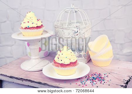 Tasty cup cakes with cream on wooden table