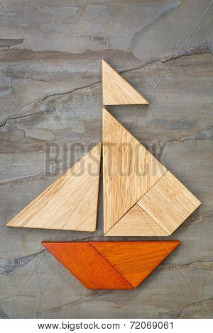 abstract picture of a sailing boat built from seven tangram wooden pieces over a slate rock background, artwork created by the photographer