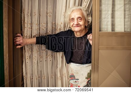 Old woman looking out of the door
