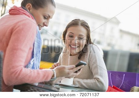 Happy young woman showing text message to friend at sidewalk cafe