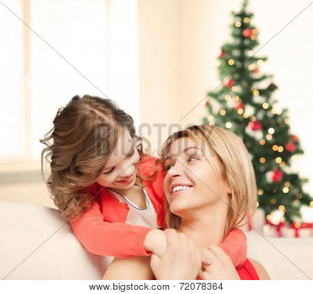 christmas, x-mas, winter, happiness concept - hugging mother and daughter
