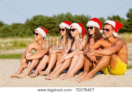 friendship, happiness, summer vacation, holidays and people concept - group of friends in santa helper hats sitting on beach