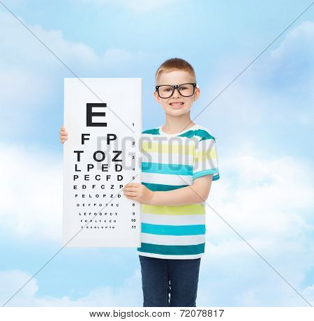 vision, ophthalmology, childhood and people concept - smiling little boy in eyeglasses with with eye chart over cloudy sky background