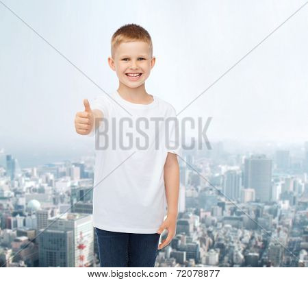 advertising, people and childhood concept - smiling little boy in white blank t-shirt showing thumbs up over city background