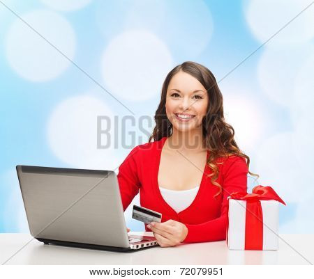 christmas, holidays, technology and shopping concept - smiling woman with credit card, gift box and laptop computer over blue lights background