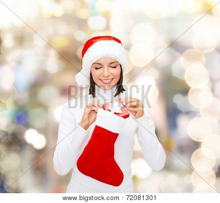 christmas, winter, happiness, holidays and people concept - smiling woman in santa helper hat with small gift box and stocking over lights background