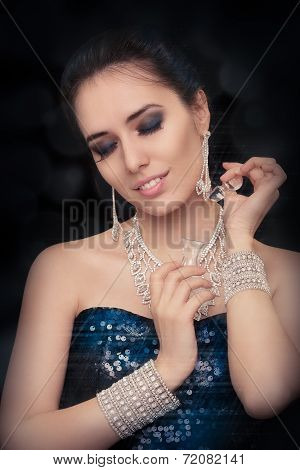 Retro glamour woman holding vintage perfume bottle wearing silver accessories