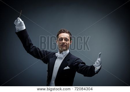 Young conductor in a tuxedo in studio