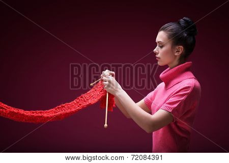 Young girl knits a scarf