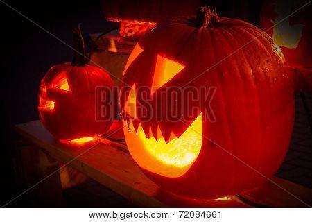 Smiling hand carved Halloween pumpkin glowing in the dark.