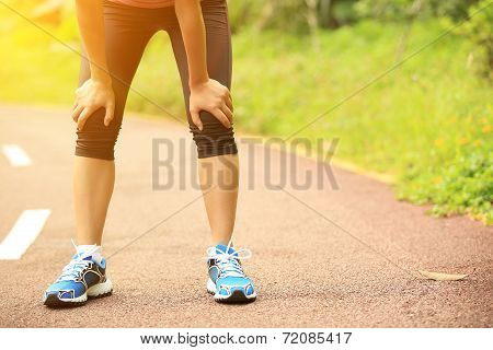tired woman runner taking a rest after running hard in countryside road. sweaty athlete after marath