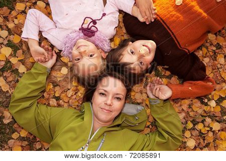Woman with kids laying on the autumn ground covered with yellow leaves