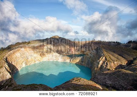Steaming Voulcanic Colorful Lakes In Kelimutu Kraters On A Bright Summer Day With Picturesque Clouds