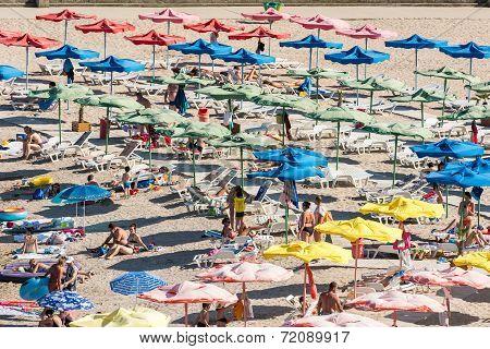 People Relaxing Under Beach Umbrellas