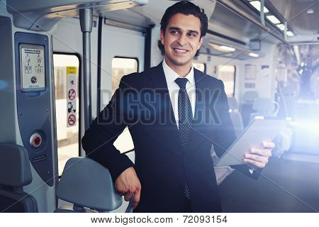 Businessman working with tablet during going to work in train