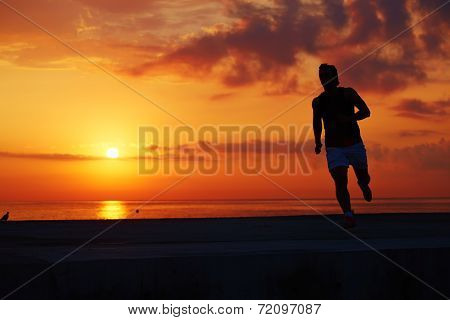 Silhouette of sportsman in action on orange sunset and sea background, morning training on the beach