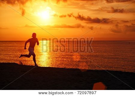 Muscular jogger silhouette running with speed along the beach
