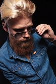 picture of long beard  - Long beard man in blue shirt looking down and fixing his sunglasses - JPG